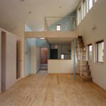 ダイニング・キッチン:床暖房を設け、桧の無垢フローリングでナチュ ラルな仕上り。 傾斜天井の大きなワンルーム空間で、南側ハイサイド ライトより明るい自然光が入る。左側階段と仕切りは収納になっていて、間を開 けてガラス棚を設けています。 奥はキッチンで、上部はロフトです。