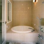 [バスルーム]円形のバスタブと石張りの洗い場。天井にはスピーカーが埋め込まれ、心地よい音楽が流れる