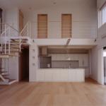 リビングよりダイニング・キッチンを見る:玄関から入ると大きな吹抜空間が広がります。 床材はメープルの明るく幅広フローリングが心 地良く感じられます。 外断熱とオリジナル仕様の蓄熱式床暖房 (温水)で家全体が暖かいです。