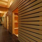 内路地見返し(夕景):25mm厚の杉板を目透しで貼り、薄いグレーに塗装して横の流れを強調。4ヶ所の各室への躙り口と板のスキマからの明かりが非日常的なシーンを演出。2Fの開放的な空間に対して、ダーク(アンダーな)で迷宮的なイメージを意図しました。