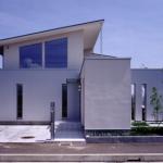道路側外観:ファサードは道路に平行にガルバリウム鋼板の外壁を設け、対比して塗り壁のエントランス部分が直行して突き 出して伸びやかさを表現。奥の吹抜部分は軒の 出を深くして奥行感を表しています。