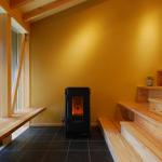 大階段&土間ギャラリー(1):この家には玄関がないですが、土間と長いベンチがあります。土間の床は黒い艶消しのタイル貼り、正面の壁は珪藻土で藁スサ入りの土壁風で10色ほど色見本を作って選定し、塗り方もこだわりました。 正面にある大型のペレットストーブの輻射熱で、真冬でも家中が心地良く暖かくなります。左側は全面に大きくガラスを嵌め込み、筋交も表しのデザインにしています。