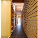 路地見返し:和室側から見返すと、玄関土間まで抜ける目線が清々しく、この長さで小さい家を伸びやかに感じさせます。左側は壁厚を利用した文庫本棚で、収納量はかなりあります。