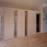 階段側との間の収納:階段室との仕切を兼ねていますが、上部は繋がってます。スリット状に開けた部分にガラス棚を設けています。
