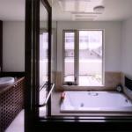 B1F 洗面・浴室:半地下の水廻りは、オープンなスペースにモダンなバスタブや洗面器が調和し、リゾートホテルのように寛げる。外には露天風呂を設けた。